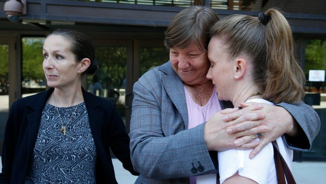 Former Austin Assistant Principal Diane Thomas, center, hugs her pastor as her lawyer, Sherilyn Ann Bunn, answers questions regarding the mistrial that was declared Wednesday morning.