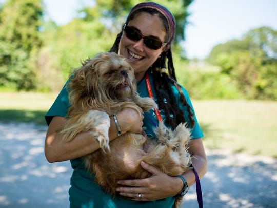 Executive director Carley Faughn holds a dog named Wookie at Acadiana Animal Aid, formerly known as Lafayette Animal Aid, in Carencro, La., Wednesday, Sept. 23, 2015.