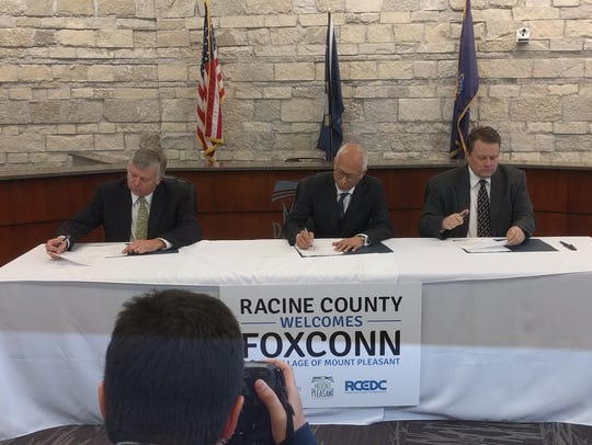 Mount Pleasant Village President Dave DeGroot (from left), Louis Woo of Foxconn and Jonathan Delagrave, Racine County executive, sign development agreements with Foxconn Technology Group in Mount Pleasant.