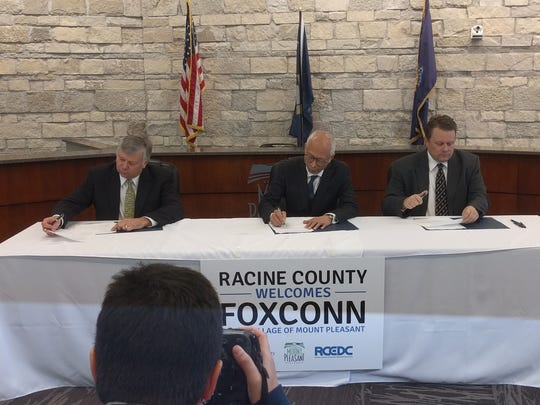 (LtoR) Mount Pleasant Village President Dave DeGroot, Louis Woo of Foxconn and Jonathan Delagrave, Racine County executive signing development agreements with Foxconn Technology Group in Mount Pleasant.