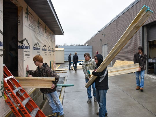 Milaca High School students carry lumber into the school's project house Wednesday, Oct. 26, in Milaca. Students are involved in all aspects of the house's construction during the school year.