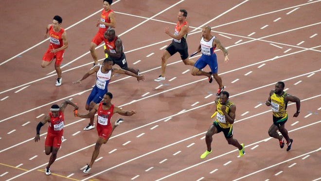 FILE - In this Aug. 29, 2015, file photo, United States' Mike Rodgers, left, takes the baton from Tyson Gay outside of the designated handover zone in the men's 4x100m relay final at the World Athletics Championships at the Bird's Nest stadium in Beijing. Team USA was disqualified. The buzz in U.S. Olympic circles is about bringing the 2024 Games to Los Angeles. A more urgent matter: Bringing home the most medals from next year's Olympics in Rio de Janeiro.  That may not be a sure thing, especially considering the struggles of the U.S. swimming and track teams this summer. (AP Photo/Wong Maye-E, File)