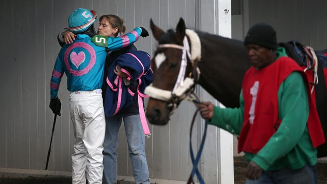 Trainer Kathleen Babcock gives a hug and kiss to her jockey, Wilfredo Rohena, before he climbs aboard her horse, Arrhythmic, at Finger Lakes Gaming & Racetrack in Farmington back in October.