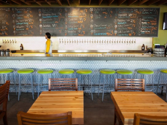 A chalkboard listing the beers on tap hangs above the