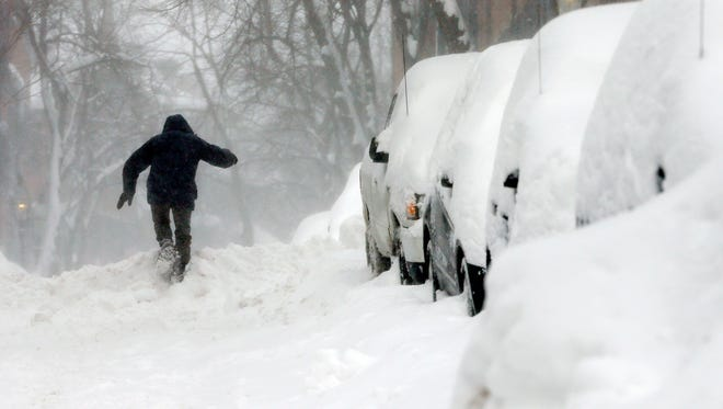 A man struggles through the snow on Beacon Hill in Boston, Sunday, Feb. 15, 2015. The Old Farmers Almanac is predicting another cold, snowy winter for New England.
