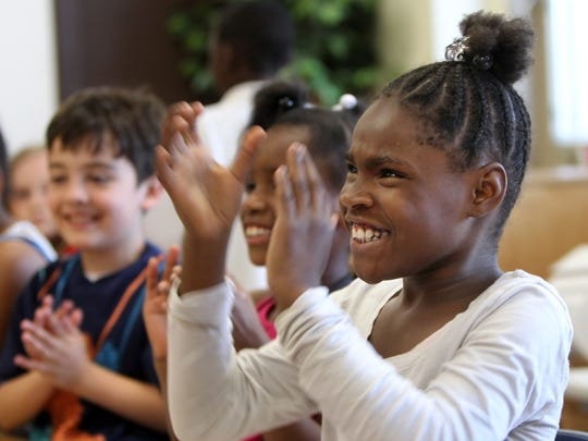Hyde Park School student Ty'Asia Andrews applauds as one of her classmates receives an award.