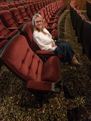 Lean back and enjoy the leg room. Theater owner Debra Neil sits in one of the new seats. The carpet is also new.