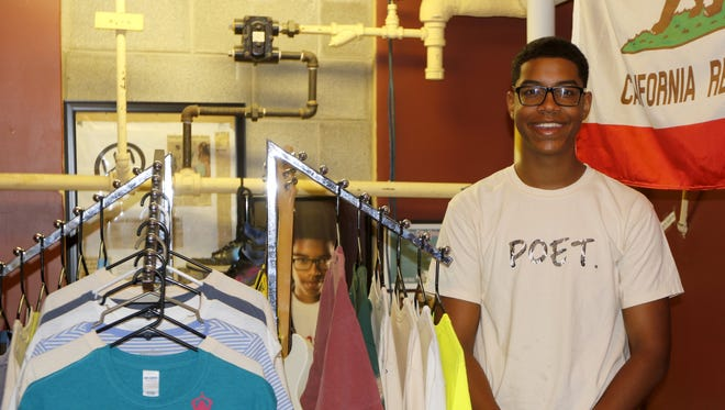Cairo Shazer of Elmira stands next to some of his Poet brand T-shirts at the room he uses to put his creative touch on them at Lake Street Presbyterian Church in Elmira.