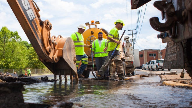 City of Staunton workers clear debris from a recently repaved section of Greenville Avenue after a water main broke on Monday, June 15, 2015.