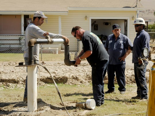 Scott Lopez, left, Sady Cass, and Nicholas Tellez, right, all with CJ Hammer Pumps, get ready to test a newly drilled well for pressure in front of Jerry Phillips' house at 1200 block of S. Spruce Road, Exeter. Phillips, center-right, was running out of water, only getting about two gallons a minute. His well was built 19 years ago and was 220 ft deep. The new well is 275 ft deep.