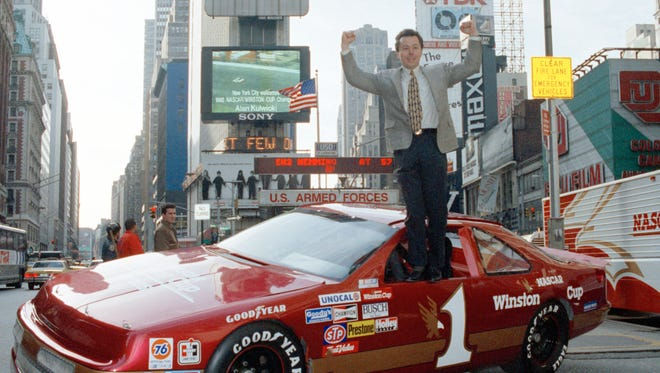 Alan Kulwicki stands on a car in New York's Times Square during the 1992 NASCAR championship celebration. Kulwicki, a Wisconsin native and the first college graduate to hold the title of Winston Cup Series champion in it's 21-year history, collected the the $1.2 million champion's prize.