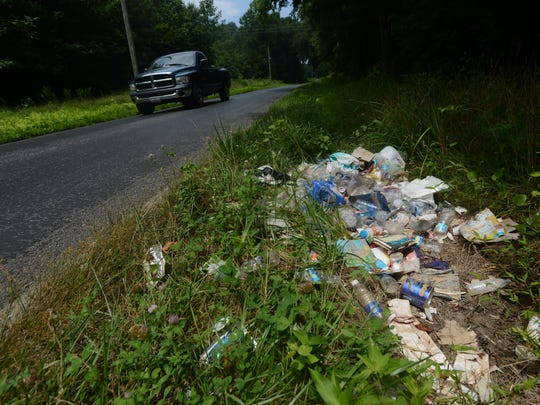 A truck passes a pile of illegally dumped trash in a ditch along Dennis Drive near Hopeton.