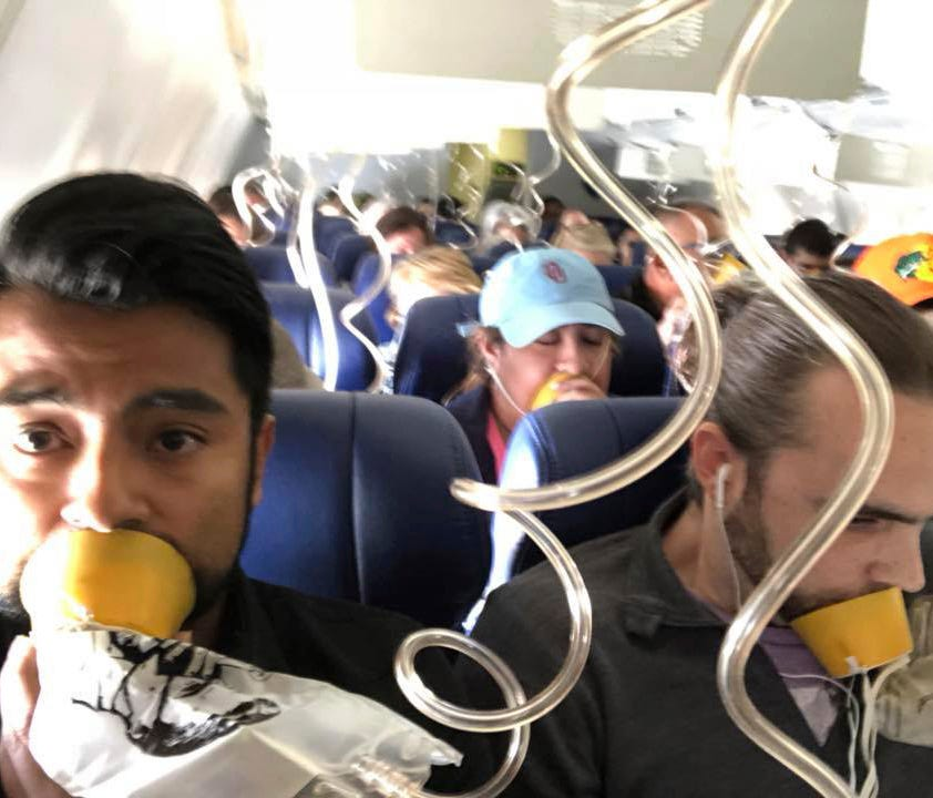 In this April 17, 2018 photo provided by Marty Martinez, Martinez, left, appears with other passengers after a jet engine blew out on the Southwest Airlines Boeing 737 plane he was flying in from New York to Dallas.