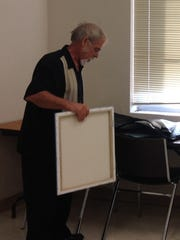 Ralph Stearns sets up a series of canvases Tuesday