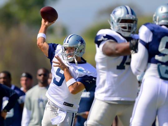 Dallas Cowboys quarterback Tony Romo (9) throws a pass as the offense runs a play during NFL football training camp on Saturday, July 26, 2014, in Oxnard, Calif. (AP Photo/Gus Ruelas)