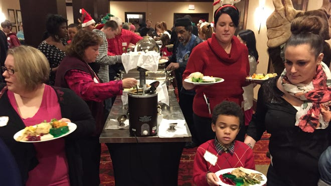 Children and adults enjoy the food at Sunday's Pomerleau party at the Hilton in Burlington.