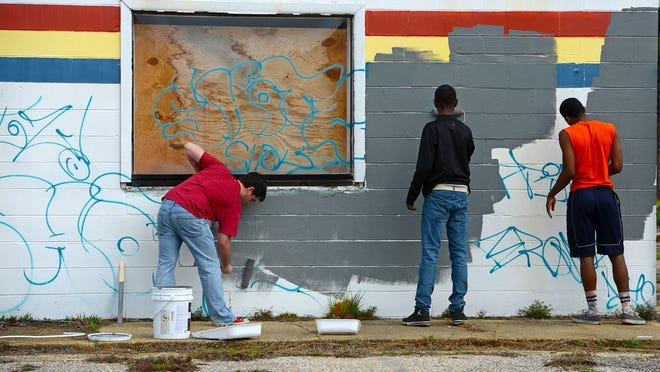 Caleb Depina, Caleb Hosie and A.J. Floyd help paint and clean up the former Myrtle Grove YMCA site Saturday morning. The Escambia High School Quarterback Club is negotiating a lease of the property to host festivals to benefit the community.