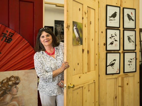 Artist Paula Van Overbeke Voris emerges  from a private space built from recycled doors at Red Door Studios. At right are bird portraits, each created in seconds, said the lifelong educator, who taught more than 7,000 students during her 25 year career as an art teacher.