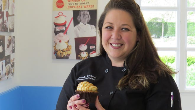 "Julia San Bartolome, who was the founding executive pastry chef for Sweet Arleen's in Thousand Oaks, is back as one of the bakery's new co-owners. She helped the business, founded by Arleen Scavone, pictured in a poster in the background, score three wins on the Food Network show ""Cupcake Wars."""