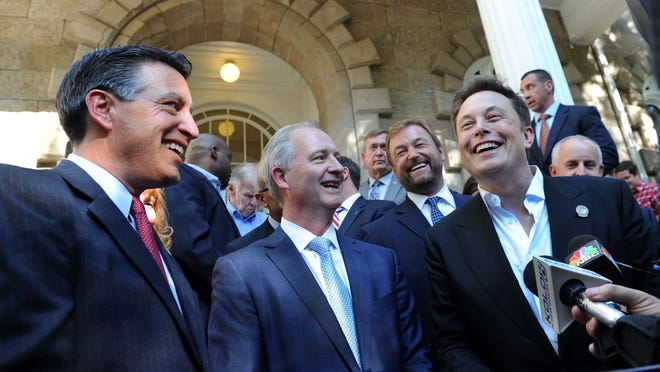 Republican Gov. Brian Sandoval, left, Steve Hill, executive director of the governor's office of Economic Development, and Elon Musk, chairman and CEO of Tesla, laugh while answering reporters questions after the press conference announcing that Nevada had been selected as the site for the Tesla battery gigafactory Thursday afternoon on the steps of the Capitol building in Carson City. U.S. Sen. Dean Heller, R-Nev., is behind Hill and Musk.