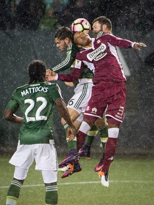 Deportivo Saprissa defender Julio Cascante (3) heads a ball against Portland Timbers forward Lucas Melano (26) during the second half at Providence Park. The game ended tied 1-1.