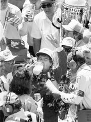 Rick Mears drinks the traditional glass of milk after winning the Indianapolis 500 in 1988 in Victory Lane.