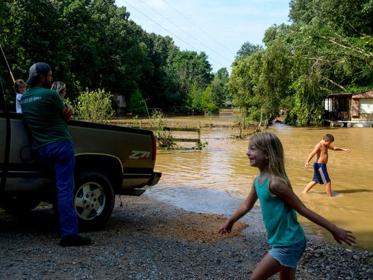 Kids try to stay in high spirits following the flooding while Ben Northcott, left, leans against his truck thinking about a plan to check homes further away in the morning hours after flash floods swept through low lands and creek beds at Swink Road in Medon, Tenn., Monday, July 16, 2018.