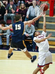 Oakland's Ray Tyler goes for a layup as Walker Valley's Zach Esinger attempts a block Monday.