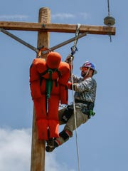 A lineman climbs a pole during the 21st annual Tennessee Valley Lineman Rodeo in June 2018.