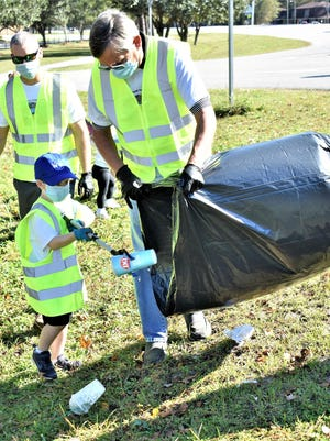 Four-year-old Hudson Burk finds it important to clean up plastic and other trash. [Steve Scholar