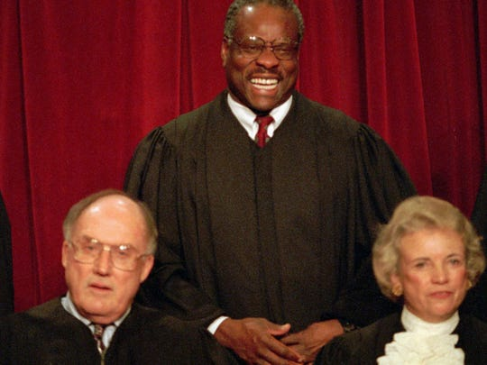 Associate Supreme Court Justice Clarence Thomas laughs