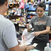 Cashier Stey Iro places a pack of cigarettes into a customer's bag after a purchase at the Joy Market in Tamuning on Monday, Dec. 1.
