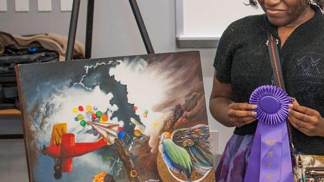 "Daeshika Smith poses with her award winning painting, ""Creation."""