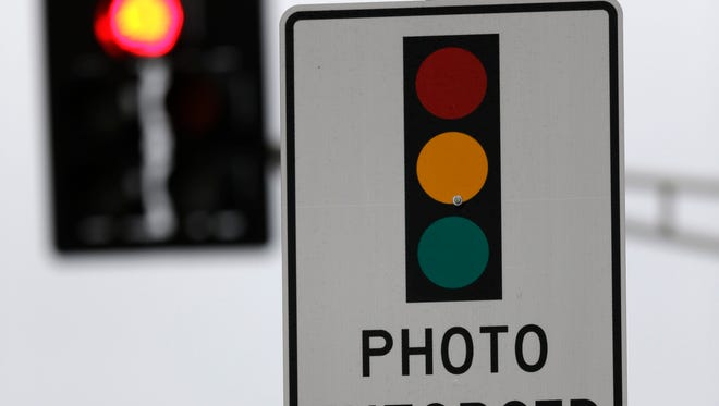 A sign warning of a photo-enforced red light camera.