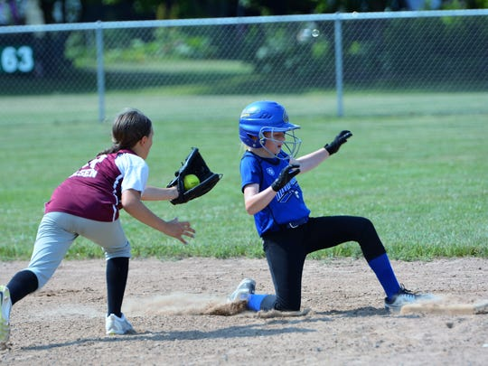 Jackie Vizer safely gets back to second base after hitting a double in the 10-and-under  game against Menominee on Saturday, June 30, in the annual Oconto Youth Softball Tournament at Holtwood Park.