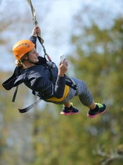 Worker Sam Lasee, 19, of Abrams takes a photo while traveling down the line at the zip line at NEW Zoo Adventure Park in Suamico.