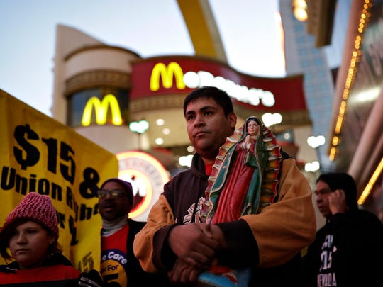 Martin Macias-Rivera holds a statue as he and others protest for a higher hourly wage for fast-food workers near a McDonald's along the Las Vegas Strip in November.