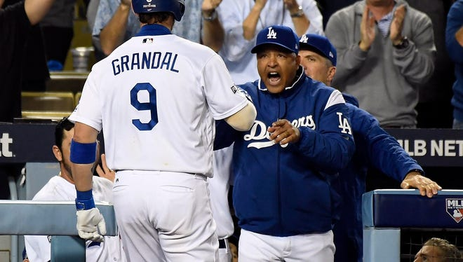 Los Angeles manager Dave Roberts celebrates after a home run by catcher Yasmani Grandal.