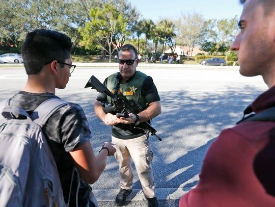 Un estudiante dialoga con un elemento del SWAT en las inmediaciones de la escuela.