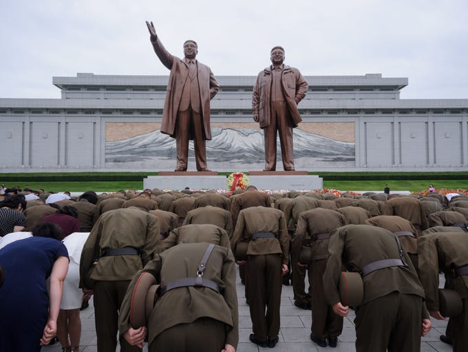 Korean People's Army soldiers bow before the statues