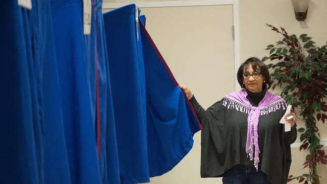 Ollie Thomas, a volunteer machine clerk, holds open a voting booth curtain for the next voter at the Dover Elks Lodge #1903 in Dover during election day.