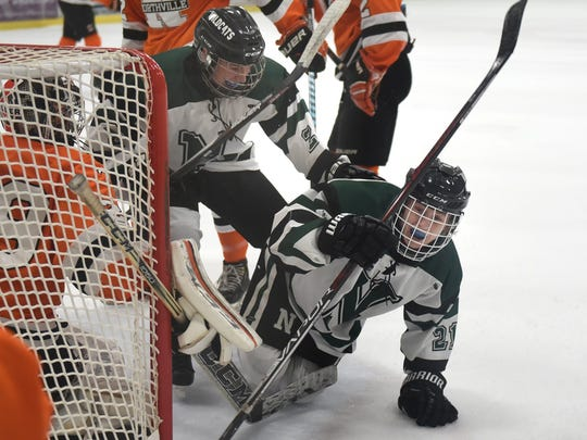 Novi's Evan Chippa (right) scores with just 48 seconds left in the first period to tie the game.