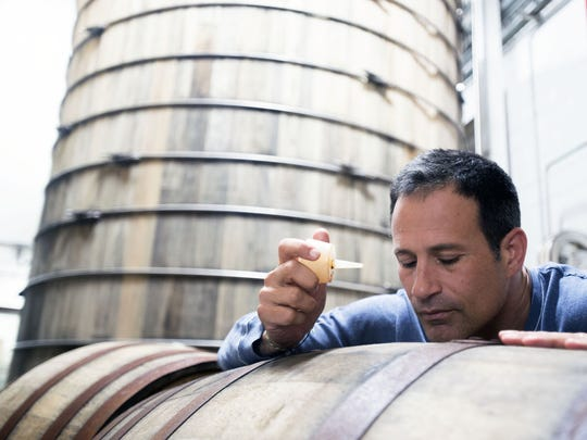Sam Calagione checks on an barrel inside the Dogfish Head brewery in Milton. Calagione's Dogfish Head Craft Brewery is a local, post-Prohibition success story.