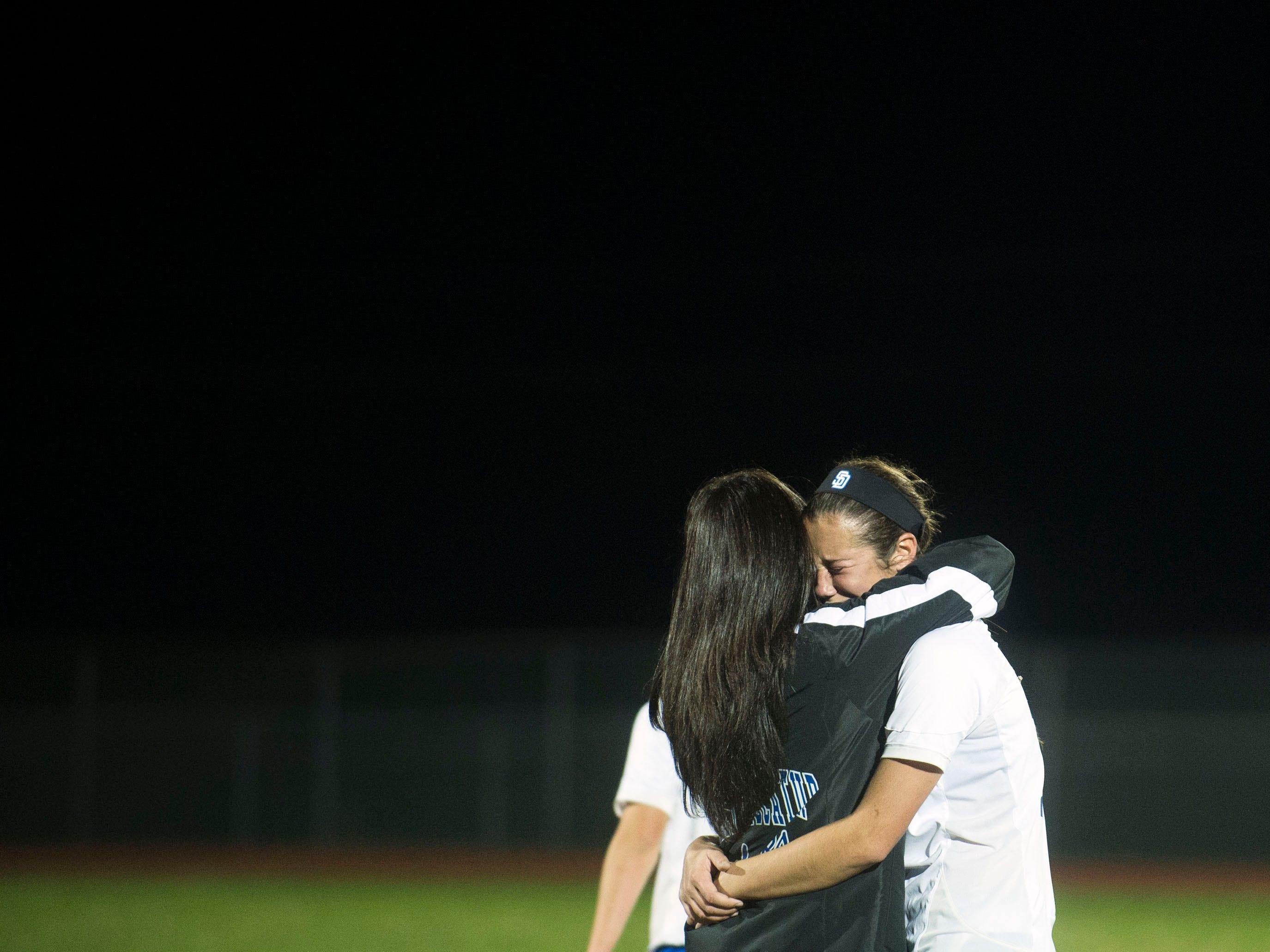 Decatur's Payton VanKirk hugs head coach Maggie Berke after a 3-1 season-ending loss over Northern Thursday night in Berlin.