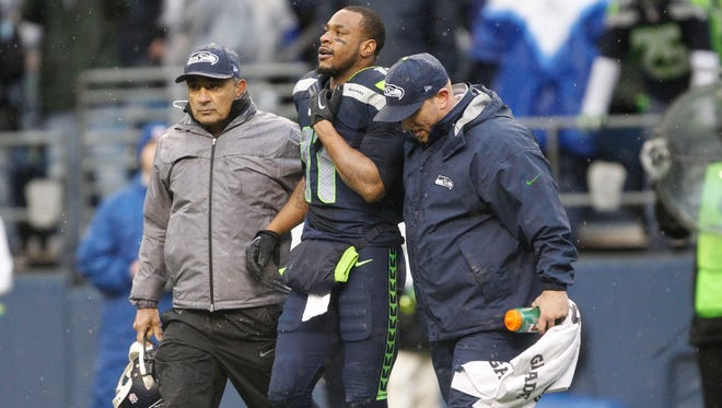 Seattle Seahawks wide receiver Percy Harvin (11) is helped off the field by medical staff members against the New Orleans Saints during the first half of the 2013 NFC divisional playoff football game at CenturyLink Field.