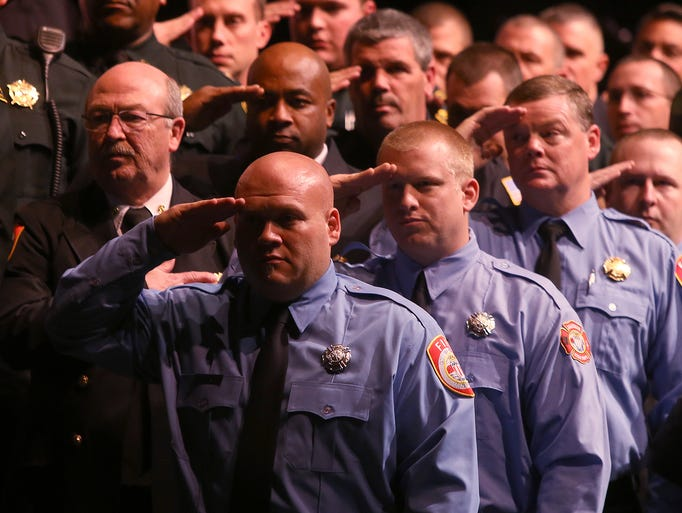 First responders salute the flag during the third annual