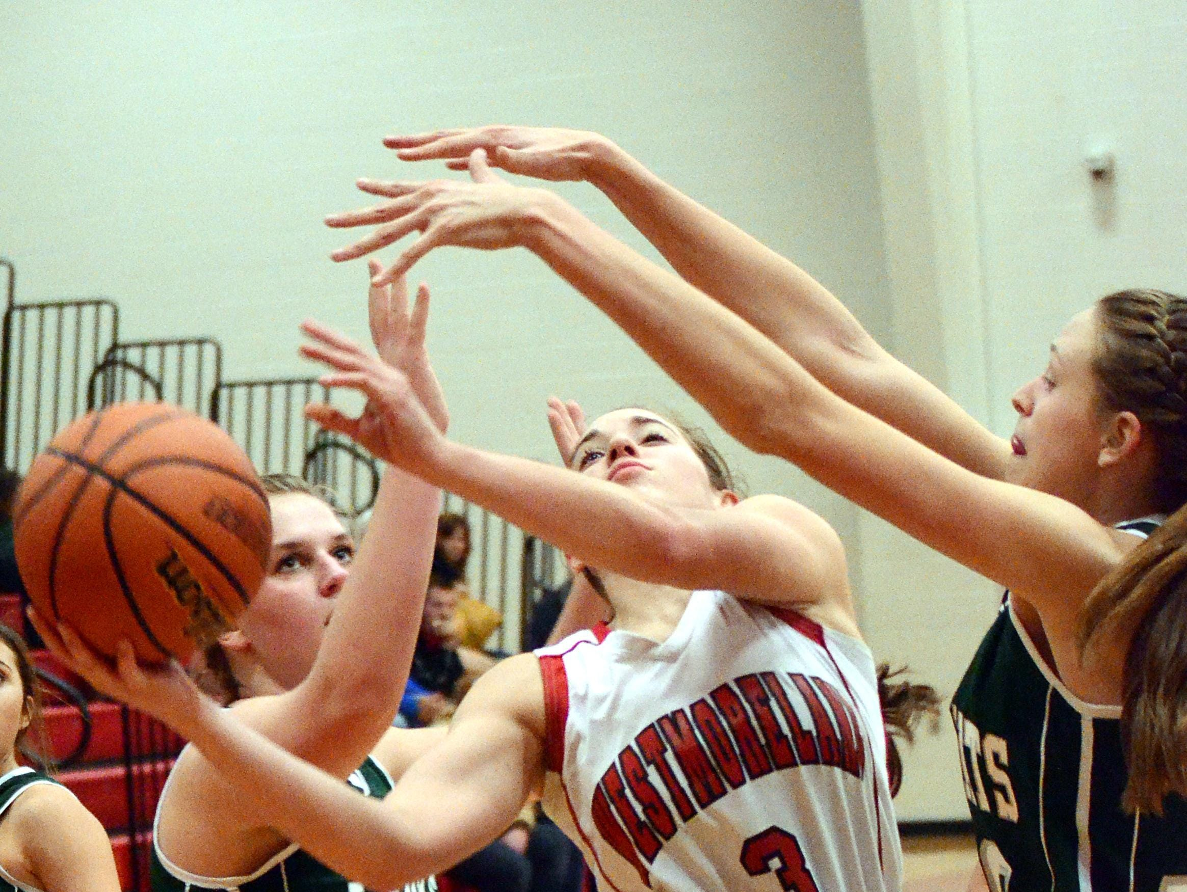 Westmoreland High junior point guard Gracie Oliver elevates for a third-quarter layin between Greenbrier junior Anna Stainback (at left) and sophomore Haley Ralph. Oliver scored four points in the Lady Eagles' 40-29 victory on Friday evening.