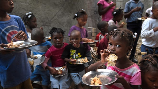 Children at an orphanage in Gressier, Haiti, eat chicken raised by KORE Foundation farmers. The chicken serves as a source of protein to combat malnutrition.