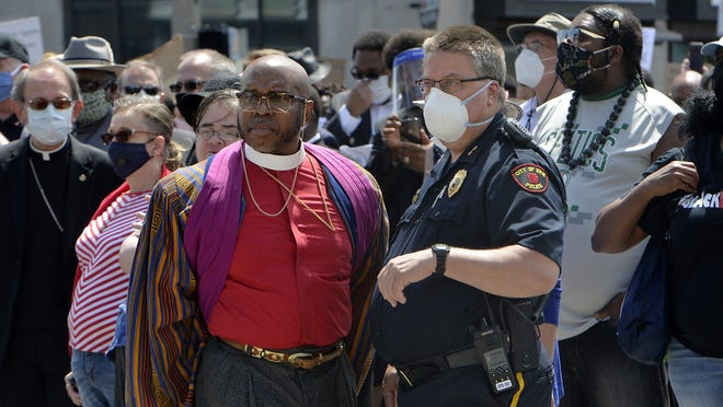 Bishop Dwane Brock, center left, and Erie Police Chief Dan Spizarny talk just prior to a silent march north on State Street on June 6. Erie Catholic Bishop Lawrence Perisco, far left, is shown in the background. Brock organized the march and more than 2,000 people walked from 11th and State streets to Perry Square.