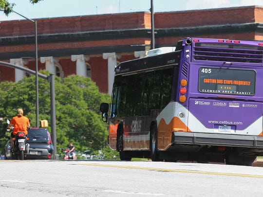 A man riding a moped passes a CAT bus near Sikes Hall in Clemson on Tuesday. Clemson city officials are discussing how best to deploy CAT in the future to address transit needs, as well as parking and traffic headaches around the city and the Clemson University campus.